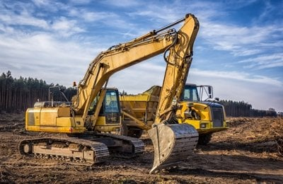 Excavator and dump truck on a new road construction NJ